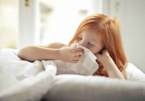 a young girl blows her nose into a tissue