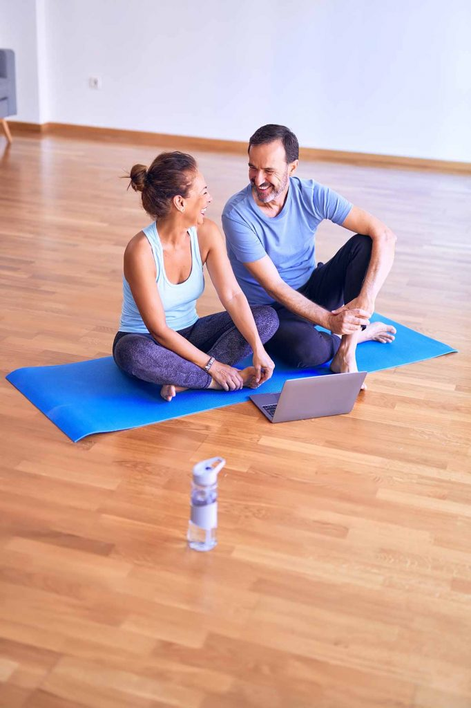 A middle aged woman and middle aged man share a yoga mat and a laugh